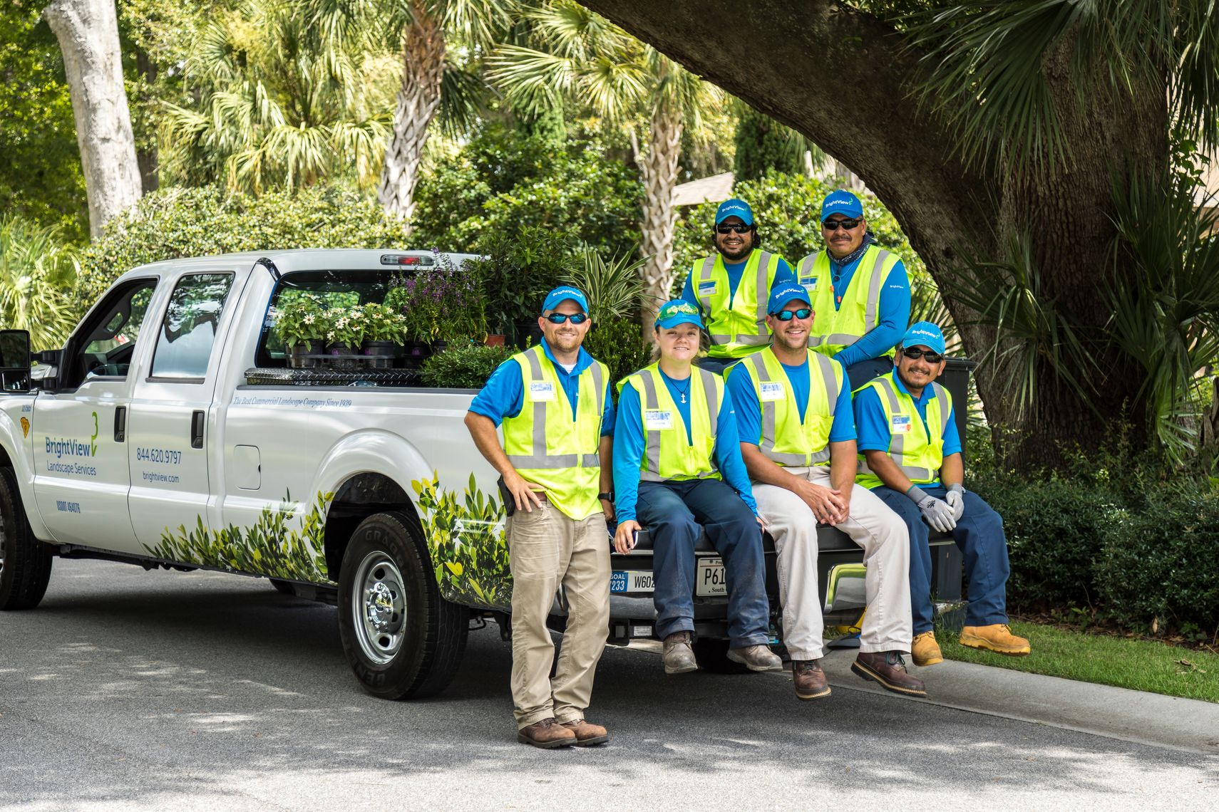 landscape maintenance crew sitting on truck tailgate