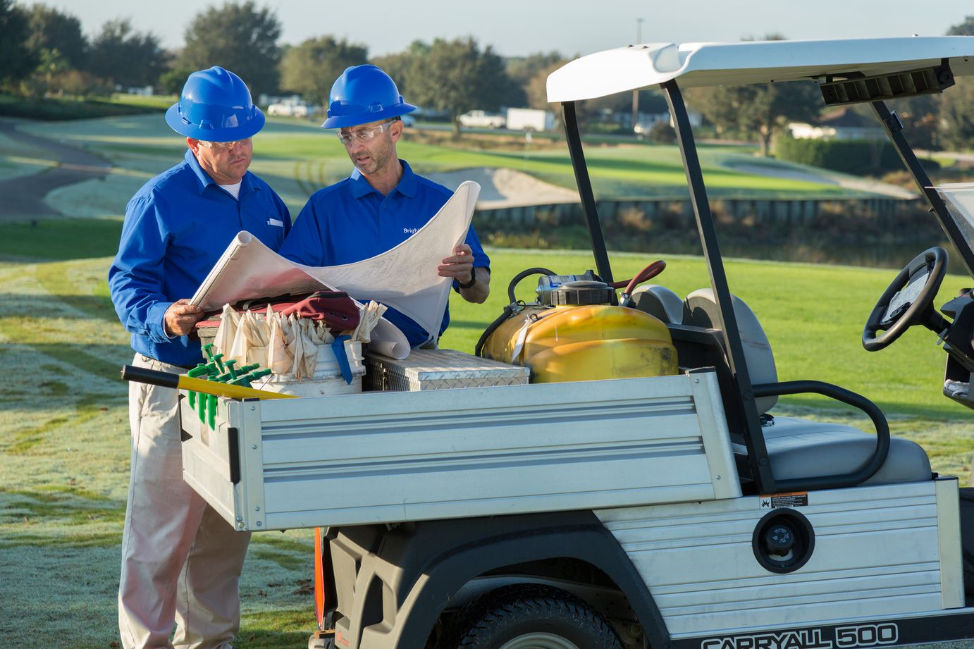 two golf course crew members reviewing a blueprint