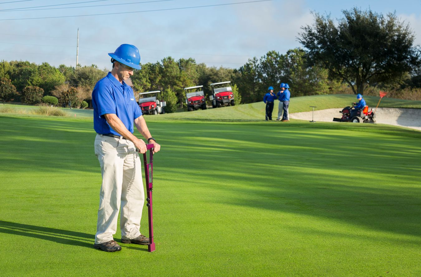agronomist collecting a soil sample on a golf course