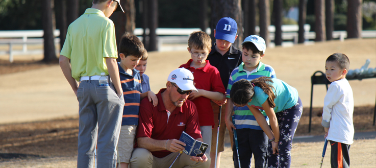 golf instructor talking with young golf students