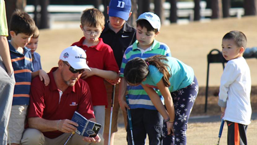 golf instructor talking to young golf students