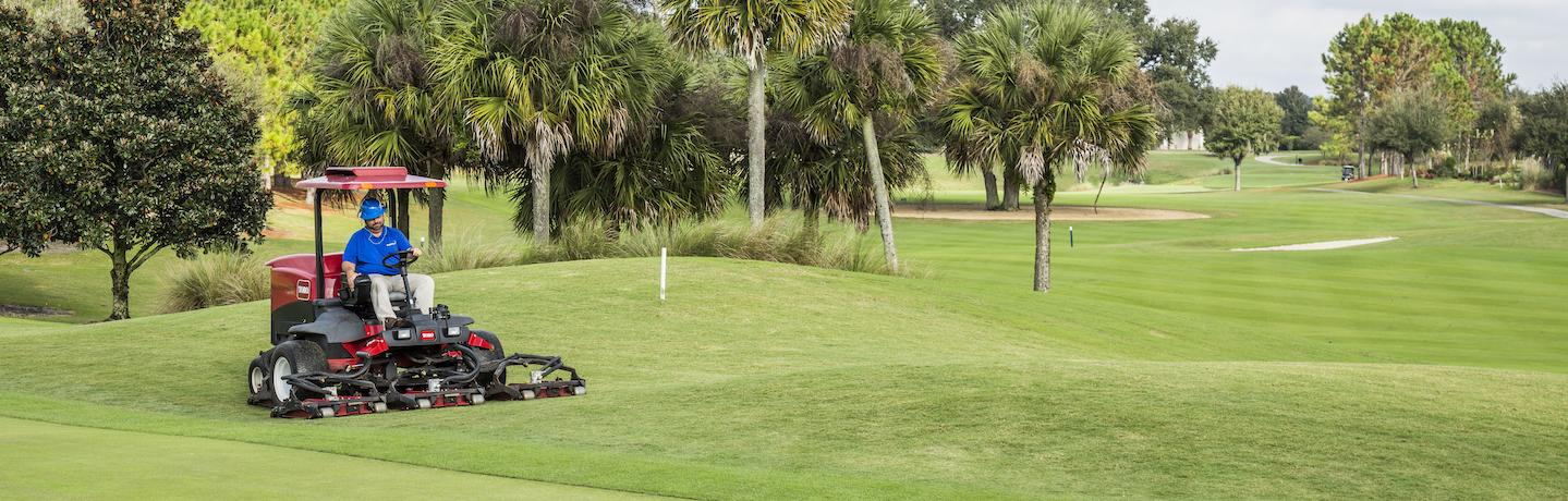 Crew member operating mower on golf course