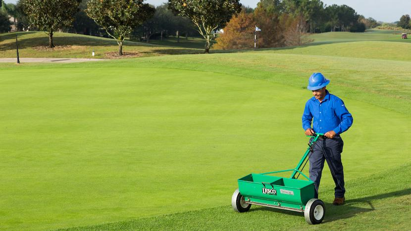 golf course maintenance crew member operating a spreader