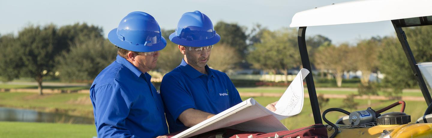 two golf course maintenance crew members discussing a blueprint