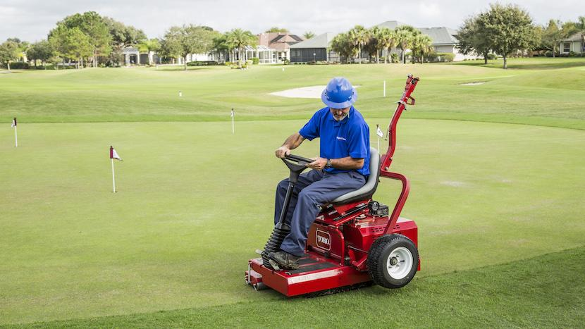 golf course maintenance crew member operating a roller
