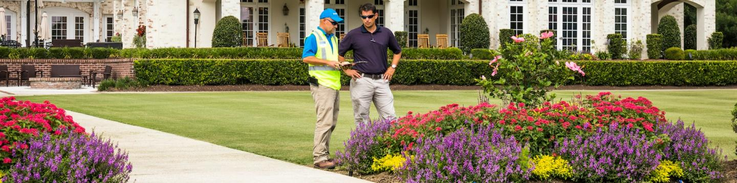 property manager and account manager examining flower bed