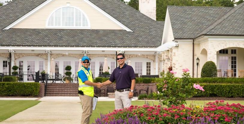 landscaper and property manager shaking hands on lawn