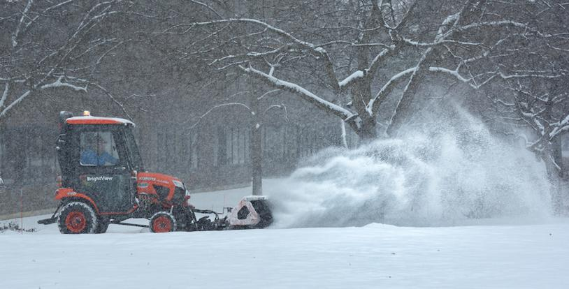snow plow with trees in the background